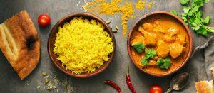 Un assiette de riz a coté d'une assiette de poulet avec des épices curry