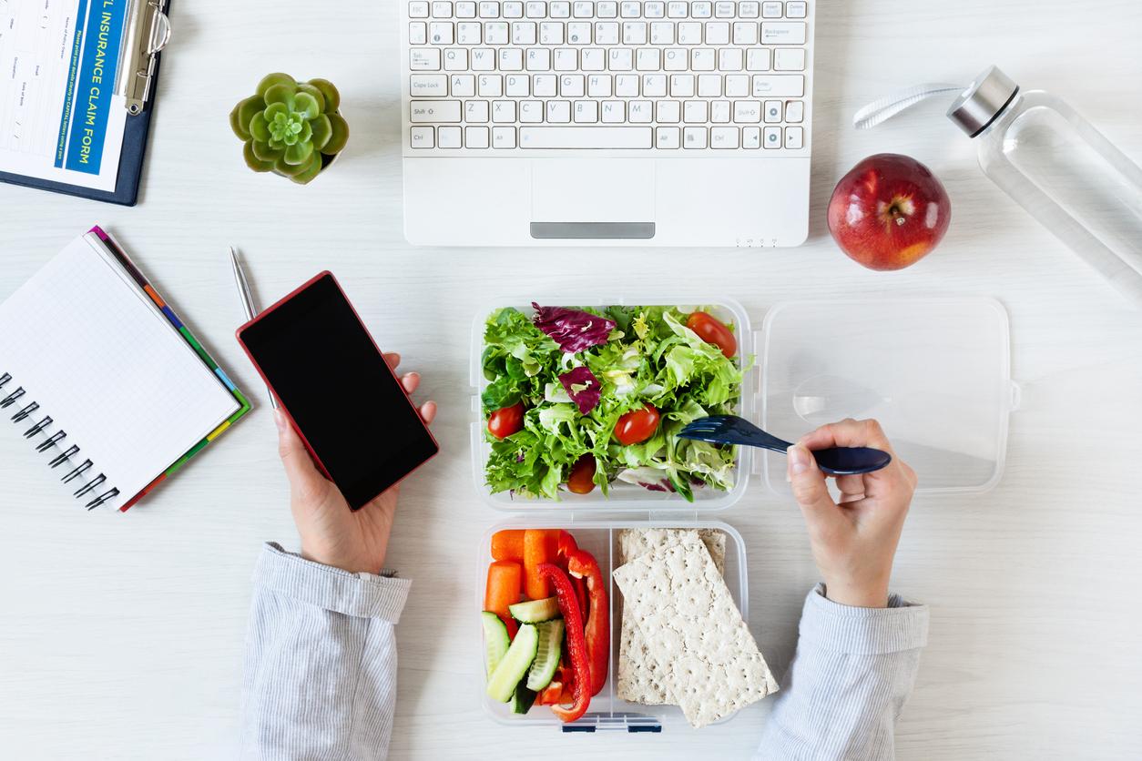Une personne entrain de manger dans son tupperware devant son ordinateur