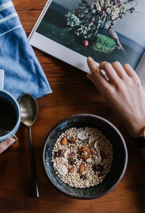 Des mains avec un café, un bol de céréale et un magazine