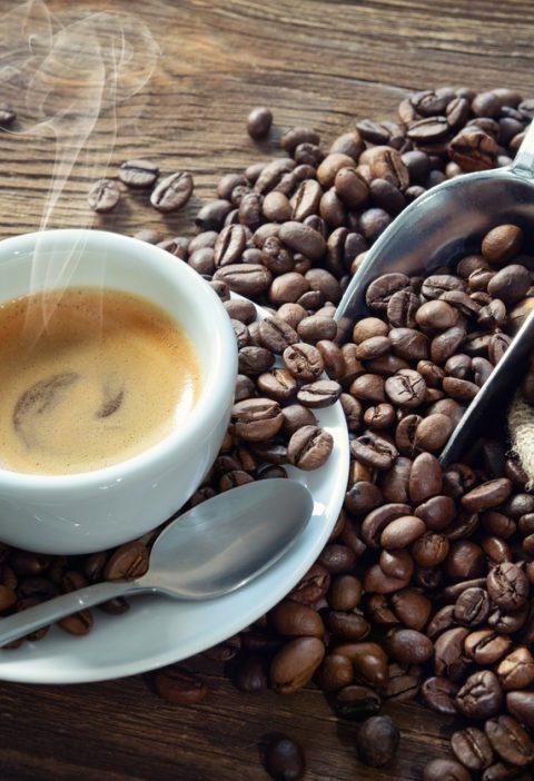 une tasse à café à coté de grains de café
