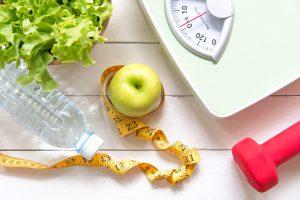 une pomme avec bouteille eau, une balance et une haltère sur une table
