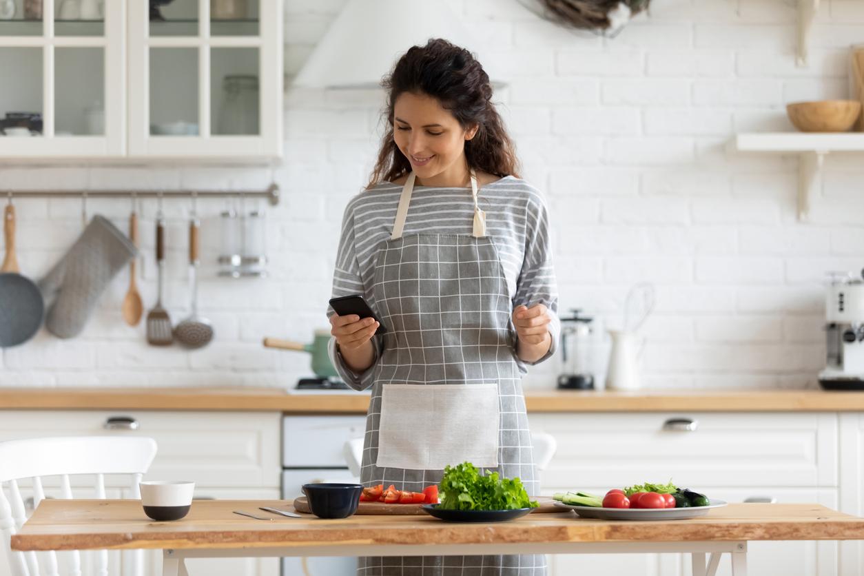 une femme qui cuisine avec son téléphone